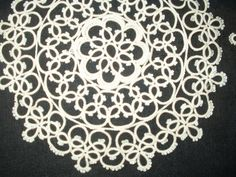 Two vintage matching pattern tatted lace doilies, although each of a different size. Off white or ivory in color, the doilies appear never to have been laundered and possibly never used. The smaller
