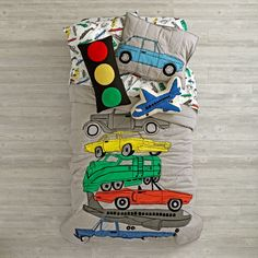 Being stuck in traffic has never been more comfortable, thanks to this exclusive transportation bedding. Made from super soft, 100% cotton, the quilt features a variety of classic vehicles. Add the coordinating sham and sheet set, and your bedroom will be stylish and road-ready.<br /><br /><NEWTAG/><h2>Details, details</h2><ul><li>Nod exclusive</li><li>Quilt available in twin and full/queen</li><li>Quilt features grey base with multi colored cars/planes/trains appliquéd and embroidered on…