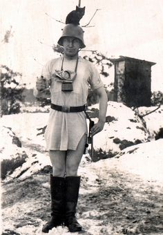 """A German sentry, bravely armed with only a bayonet, a nightshirt and the kampfkatze """"Fritz"""". A latrine can be seen in the background."""