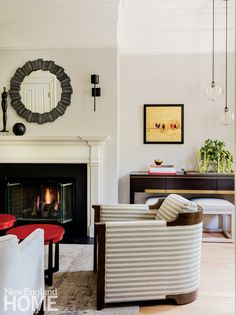 """Designer Nicole Hogarty orchestrated the view from the front door as a welcoming vignette that hints at the unexpected with the inclusion of the bright-red coffee tables and bulbous pendants. """"There's no foyer, so it was important for me to create a small moment there,"""" she says."""