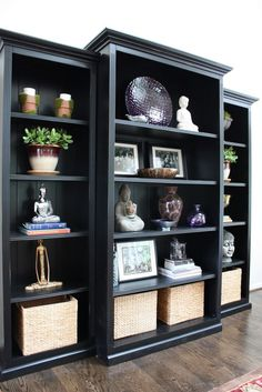 Trim three inexpensive bookcases with mouldings and paint them black… they look great!