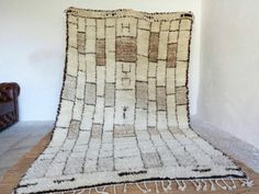 "GENUINE BERBER BENI OURAIN RUG.    Made by our weaver Atika (my sister).    🌠 Condition: New 2017.  🏳️‍🌈 Design: Brick Wall.  🎨️ Colors: Ivory Rug with Black Outline Bricks and Brown Shaded Bricks.  🐑 Materials: Natural dyed Wool.  🕸 Details: Handwoven.  💎️ Pattern: Stacked Brick.  🔶️ Pile: High.    📐MEASURES:  317cm / 190cm (3m17cm / 1m90cm) = 10.4 feet / 6.2 feet = 124"" inch x 74.8"" inch to be exact.    🎟SPECIAL BONUS WITH ANY RUG PURCHASE:  🛍Buy any large rug ($1000 or more)…"