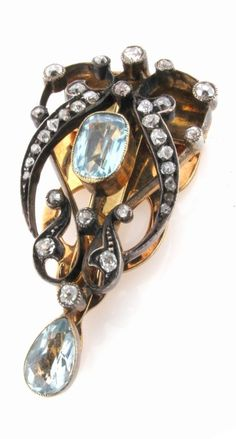 An Art Nouveau gold clip brooch, mounted with two aquamarines and graduated circular cut diamonds. #ArtNouveau #clip