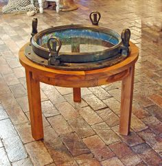 Custom made nautical table produced using an early 20th century brass four dog ship's porthole and mounted on to a round teak wood base. The porthole retains a wonderful old bronzed colored patina. Great for a small coffee or cocktail table and can be used at your home on your yacht and at the office too!