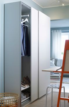 Widok na przedpokój z płytką, podwójną szafą IKEA z drzwiami przesuwanymi.