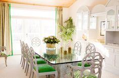 White walls, printed beige curtains, green and white chairs, and  glass dining table
