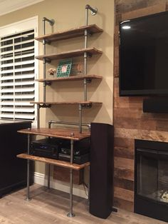 Reclaimed wood shelf for TV equipment and stereo receiver made from black pipe for a modern industrial look