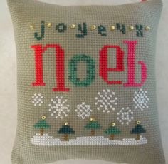 Great way to wish everyone a Joyeux Noel.   This ornament is cross stitched on dark khaki aida,backed with muslin, and stuffed with polyfil. It has a red ribbon hanger and is trimmed with tiny gold beads.  Approx. 4 x 4.  Design by Lizzie Kate.  Great for your tree or a knob this Christmas.