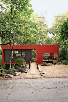 A steel footbridge grants this cost-conscious Atlanta home street access. Its striking facade is made of fiber-reinforced concrete painted red. Photo by Gregory Miller. Courtesy of Gregory Miller . This originally appeared in An Affordable Modern Home in Atlanta .