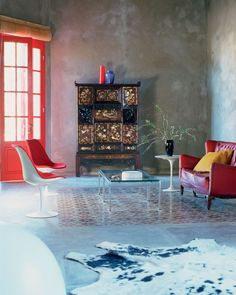 cement walls, cowhide rug, cement floor, sofa, chairs, coffee table, chinoiserie cabinet
