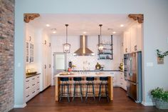 The newly configured kitchen has a large center island, crisp white cabinetry with contrasting black hardware, new stainless steel appliances and custom vent hood. Joanna found vintage wooden corbels at a local salvage shop for the perfect finishing touch.