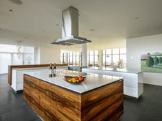 Who wouldn't want to party in this dramatic penthouse kitchen, with a panoramic view of the sprawling cityscape? Ideal for entertaining, this modern white kitchen embraces an open layout with the adjacent dining and living spaces.