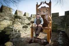 Paul Clarke, sculptor with the new Eisteddfod chair installation at Cardigan Castle - A remake of Wales' original Eisteddfod chair. The 9ft (2.7m) sculpture has been placed on top of the East Tower of the 900-year-old castle, which was the site of the first Eisteddfod in 1176.The hand-carved structure is one of the final pieces of the castle's revamp.Made from local oak, slate and bronze.