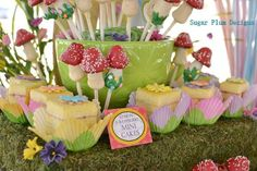 Alice in Wonderland party-The adorable mini cakes are surrounded by mushroom-shaped cake pops- such a beautiful display among the grass and flowers