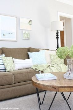 Pretty spring living room - love the mixture of green, aqua, blue and white pillows with the dark couch! And that coastal artwork gallery wall is so pretty! Living Room Decor Blue And Brown, Living Room Green, Living Room Paint, Living Room With Fireplace, Living Room Colors, New Living Room, Living Room Sofa, Living Room Furniture, Blue And White Pillows