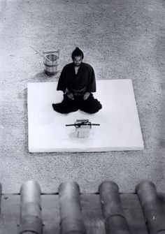 "Samurai about to commit seppuku - ritual suicide by self-disembowelment. There is usually a ""second"" close at hand, armed with a katana, and he will strike the head from the body of the suicide, as the death would be slow and agonizing. It's an ""honor"" thing..."