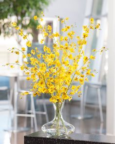 """Dancing silk Oncidium Orchid stems appear to drink from our crystal  clear acrylic water in a shapely 10"""" tall glass vase. Wonderful  brushstrokes of natural beauty that one can place easily in any interior  to create an instant focal point."""