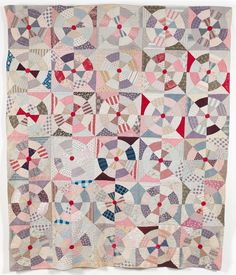 Wheels Quilt - description from the UK quilt museum - This quilt has been hand pieced and machined in roller printed dress cottons which include striped, floral and check designs to produce a wheel effect in patchwork. The quilt is machine quilted.