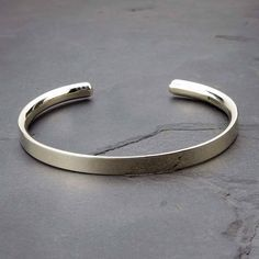 "A lovely solid silver man's bracelet, a perfect gift for men made by silversmiths in our workshop.We can engrave the inside or the outside with a message to personalise it. For an even better fit for small or very large men, measure the wrist with a tape or a piece of string and let us know the size, we will then adjust it this end before sending it outThe bracelet is 6mm wide and the silver is ""D shaped"" on the inside to a depth of 3mm making it really comfortable to wear. One recent…"