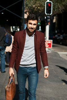 Shop this look on Lookastic:  https://lookastic.com/men/looks/blazer-v-neck-sweater-long-sleeve-shirt-skinny-jeans-tote-bag-watch/11001  — Grey Long Sleeve Shirt  — Grey V-neck Sweater  — Burgundy Wool Blazer  — Tobacco Leather Watch  — Blue Skinny Jeans  — Brown Leather Tote Bag