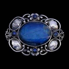 This is not contemporary - image from a gallery of vintage and/or antique objects. GEORG JENSEN (1866-1935)  A silver brooch set labradorite stone.