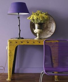 Mustard metal table against a muted purple wall.
