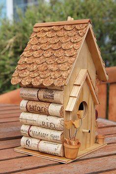 Nichoir en bois orné de bouchons en liège de bouteilles de vin et avec un toit en tuiles découpées dans une plaque de liège.
