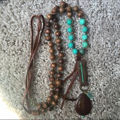 Unique turquoise & brown beaded necklace. This is a gorgeous & very unique necklace. It has leather, brown wooded beads and turquoise beads. With a turquoise painted copper cross and leather pieces. The leather also hangs down & is connected by gold clasp. I spent $199.00 on this beauty in 12/2014. It is 24 inches in length and can also be worn doubled. Very nice both ways. I doubt you will see anyone with this one of a kind necklace! Jewelry Necklaces