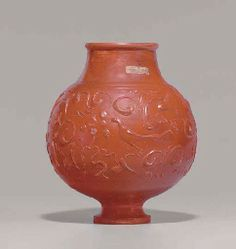 A ROMAN RED-SLIP BARBOTINE WARE VESSEL   CIRCA 2ND CENTURY A.D.   Probably from Gaul, the spherical body with a short neck and rounded rim, on a pedestal foot, decorated in the barbotine technique with ivy tendrils and scrolling, framing a peacock on either side, with dots perhaps representing clusters of grapes, the register framed by bands above and below (Christies)