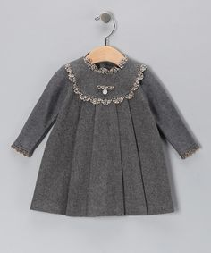 A ruffled outline gives this dress shape around the collar and shoulders, while a pretty medallion adds a subtle but elegant flourish in the center. Made with warm wool, this piece will keep little darlings feeling and looking fabulous, even in cold weather.Fabric 1: 60% wool / 35% polyester / 5% recycled fibersFabric 2: 40% acrylic / 30% merino wool / 30...