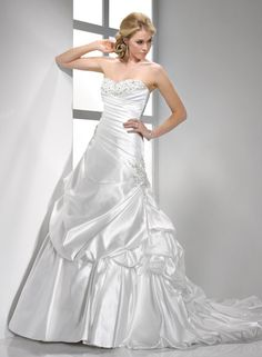 Vana - by Maggie Sottero  DESCRIPTION  Glamour and romance combine in this ravishing L'Amour Satin gown. The asymmetrical bodice with corset closure features the sophistication of Swarovski crystal embellishments accenting the sweetheart neckline and varying heights of the side skirt, while draping bustles cascade toward the bubble hem train.