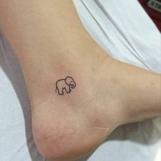 Simplista, de uma prestação de um elefante é retratado em tinta preta perto do utente calcanhar neste tatuagem.