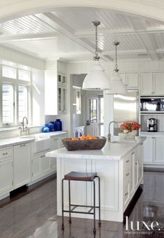 New Jersey Beachfront home. Two-inch honed Carrara marble countertops offer ample prep space for the busy kitchen, while custom Shaker-style cabinets are painted in Benjamin Moore's White Dove for a crisp effect. The white enamel industrial pendants, from Ann-Morris Antiques, help to fill the wide-open space...
