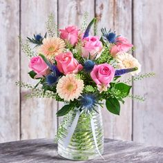 A striking bouquet of pink and peach flowers with blue eryngium and veronica, presented with a honeycomb vase.