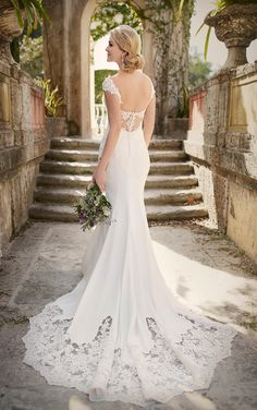 This chic crepe bridal gown from Essense of Australia features pretty lace cap sleeves, lace back detailing, and a scalloped lace cathedral train. The back zips up under fabric-covered buttons.