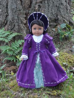 This beautiful regal outfit will fit your American Girl doll or any other similar 18 doll size.  This young Tudor Princess is ready for travel to the Royal Palace. She wears a long sleeve white chemise. The lower sleeves are gathered and trimmed with fine white lace. The neckline is high and edged with narrow lace. The chemise closes in the back with snaps. Her royal purple overgown has scrolling silver metallic embroidery and hand sewn glass pearls on the lower and upper sleeves, along the…