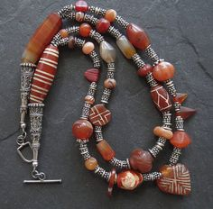 A double strand necklace full of wonderful ancient, antique and old Carnelian beads for those who appreciate old beads.  There are six etched carnelian beads of different shapes and sizes. Top center is an antique carved carnelian bead from Afghanistan. The lighter colour bead on the top row left hand side is an ancient Agate bi-cone bead from Mali, plus three antique bi-cone beads from the African trade. Also in the mix are two triangle striped top drill beads from Nigeria, an old carnelian…