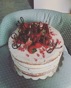 Naked cake decorated with strawberries, pomegranate and chocolate writing