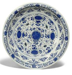 AN ENGLISH DELFT BLUE AND WHITE DISH  CIRCA 1720, PERHAPS BRISTOL.  With turn-over rim, painted with a geometric pattern of flowers, 'trekked' in black within concentric circles and scrolls 13 3/8 in. (34 cm.) diam.