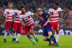 Lionel Messi of FC Barcelona fights for the ball with Mehdi CarcelaGonzalez and Matthieu Saunier of Granada CF during the La Liga match between FC...