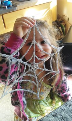 Create an awesome glitter spiderweb with this kids' Halloween craft project that takes hardly any supplies to make!