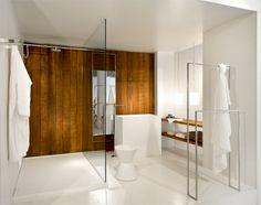 #reforma #baño con lavabo rectangular de diseño, zona de ducha con separación de vidrio, pared de madera y suelo de resina epoxi.
