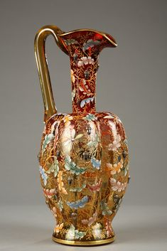 Nice polylobed ewer in Moser Karlsbad glass, in a gradient of amber to red currant, patterned with polychrome enameled oak leaves and insects. Heat applied gold and silver tassels adorn..