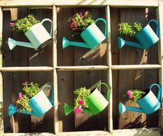 Os regadores são muito utilizados em decoração de jardins. E uma das possibilidades de décor é fazer um jardim vertical com moldura. Em cada espaço, você pode colocar um regador de cada cor para deixar o ambiente ainda mais delicado!