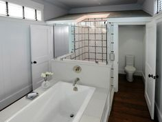 An all-over white palette paired with dark brown hardwood floors gives this bathroom a crisp, modern look. Black and gray mosaic tiles created a block pattern on the white shower walls, while a gray roof-like structure separates the space, allowing the bathtub to seem divided from the other areas of the bathroom.