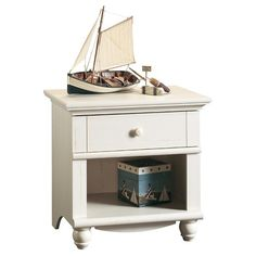 This night stand has a drawer with metal runners and safety stops that features the patented T-slot assembly system. Open shelf provides additional storage. Detailing includes solid wood knob and turned feet. Night stand comes in Antiqued White finish.
