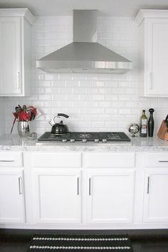 small shop Erika Brechtel white kitchen carrera marble subway tile backsplash stainless hood
