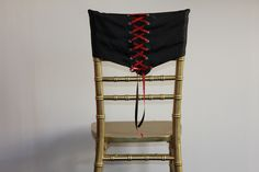 Black corset with red ribbon lace chair cover.