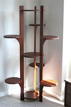 THERE IS NO SHIPPING OFFERED ON THIS ITEM- IT IS BEING OFFERED FOR LOCAL PICK-UP ONLY!  For your consideration, this is an amazing 5 foot tall (60 inches) Mid Century modern Teak wood plant stand display with 9 circular shelves. It fills a room corner brilliantly. The 3 interior shelves have a diameter of 14, and the 6 exterior shelves have a diameter of 11. It has been cared for over the years with beeswax, and has a lovely patina. The upper rear exterior shelf does have a wood split in…