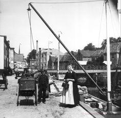 """Aan Kerkstraat wordt schip mbv stagernaat gelost, ca1897. Op achtergrond Diezerpoortenbrug, draaibrug 1870-1939. Halfronde muur links werd 1912 afgebroken, evenals Brugwachtershuisje uit 1880, dat in 1924 is afgebroken. Geheel links Almelose Veerhuis, Kerkstraat 26. Deze werd afgebroken in 1924. Rechts Marsmanpanden. Op voorgrond boerin in Sallandse klederdracht naast jongen en bakkerskar. Achter haar kist met opschrift """"The Vulcan/safety matches"""". #Overijssel #Salland"""